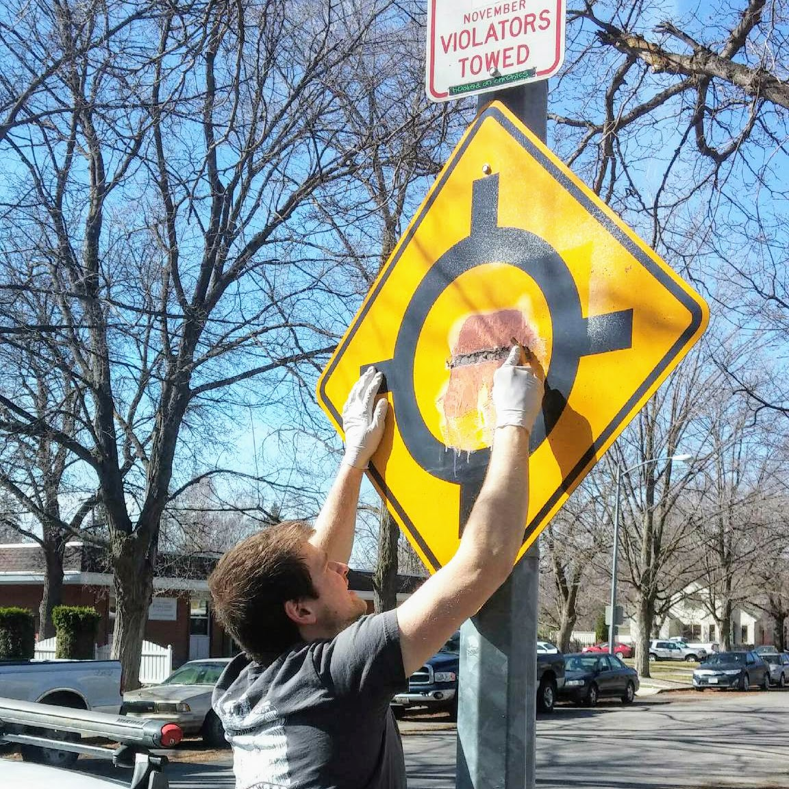 A UM student cleaning graffiti off a street sign.
