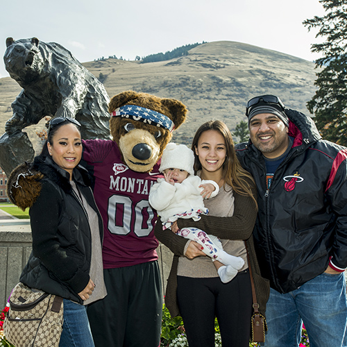 Family posing in front of the Griz statue with Monte