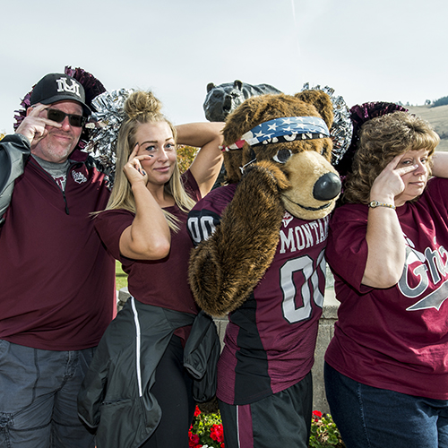 Family posing with their student and Monte in front of the Griz statue on the UM Oval
