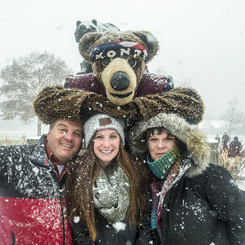 Parents posing in the snow with Monte and their student