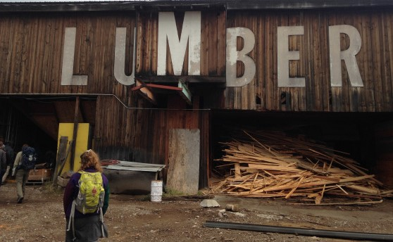 "Aspen stands before wooden building marked ""LUMBER"""
