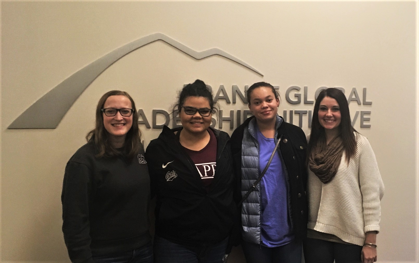 Martha Krebill, Nikia Reynolds, Anna Peterson, and Melanie Gagen stand in front of the Franke GLI Logo