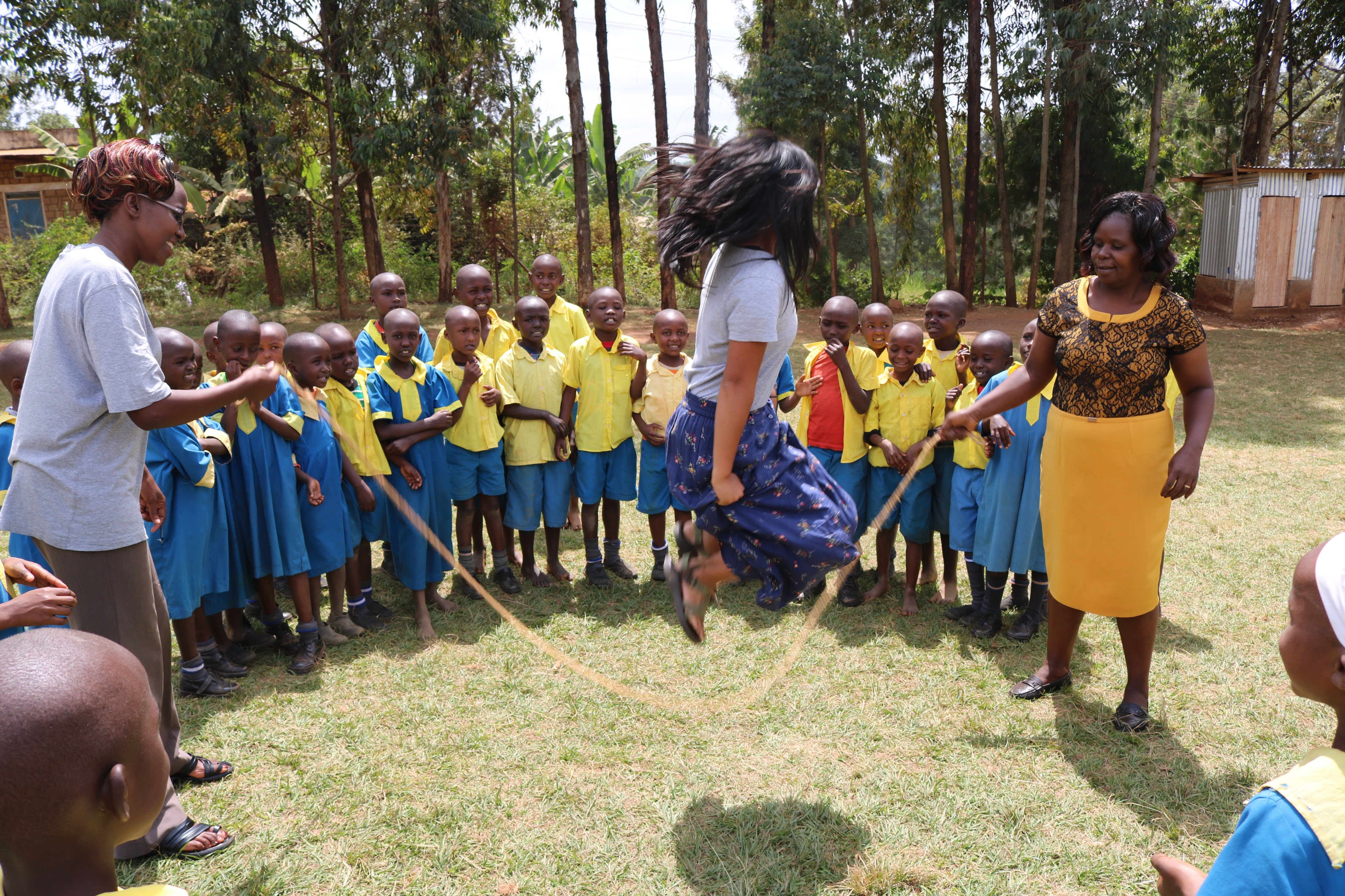 Jenny Smith jump-roping while Kenyan children watch and sing a rhyme
