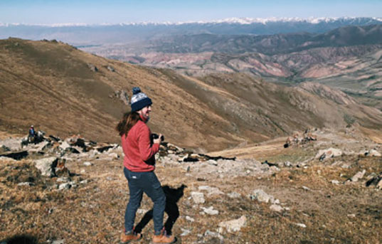 UM student Camryn Vaughn stands atop a mountain in Kyrgyzstan