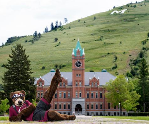 Monte, the University of Montana mascot, lies down in front of Main Hall