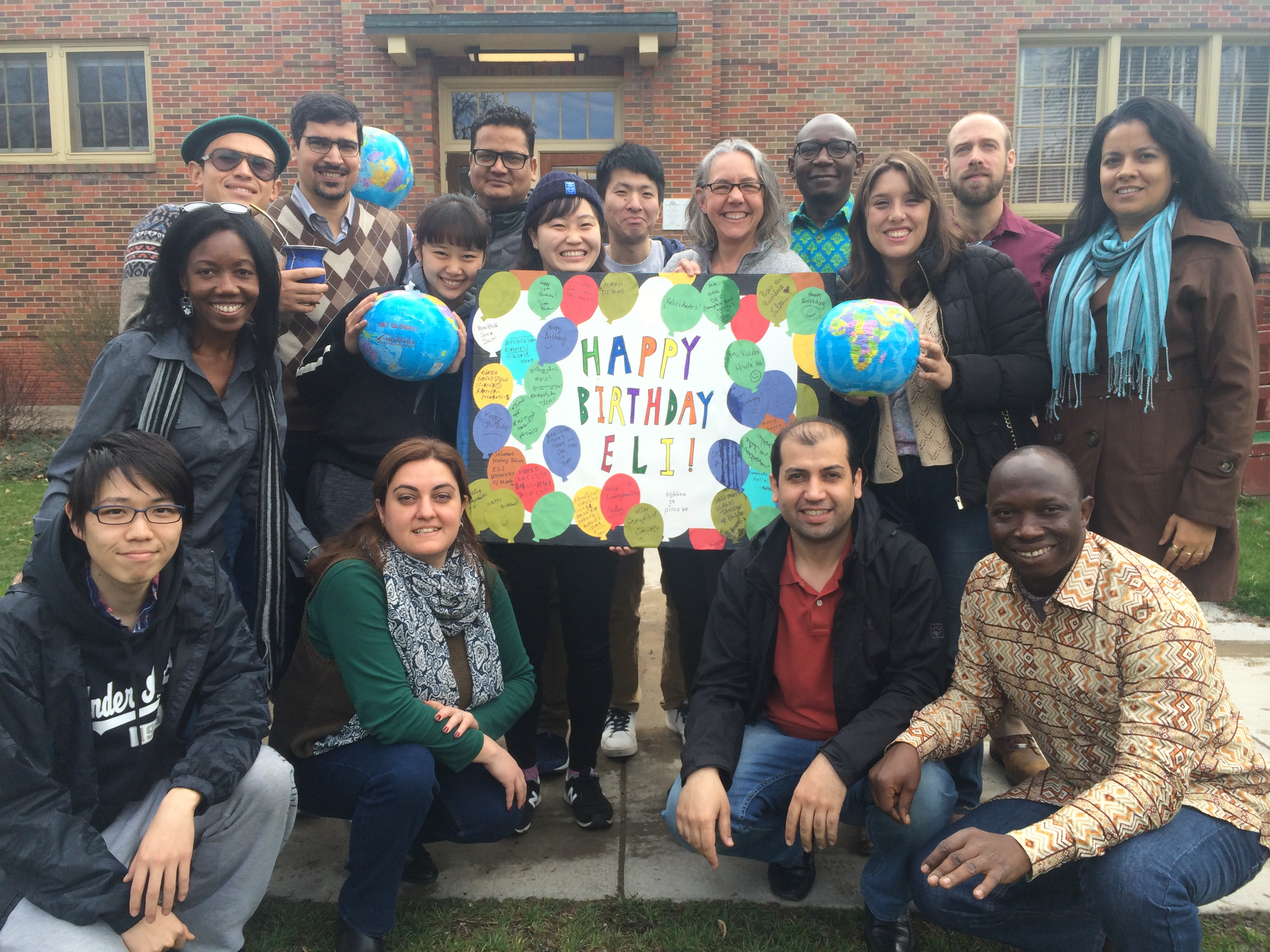 Students of the English Language Institute at UM stand with birthday poster