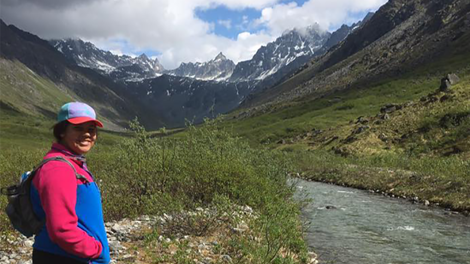 Brianna Ashley stands in front of mountains.