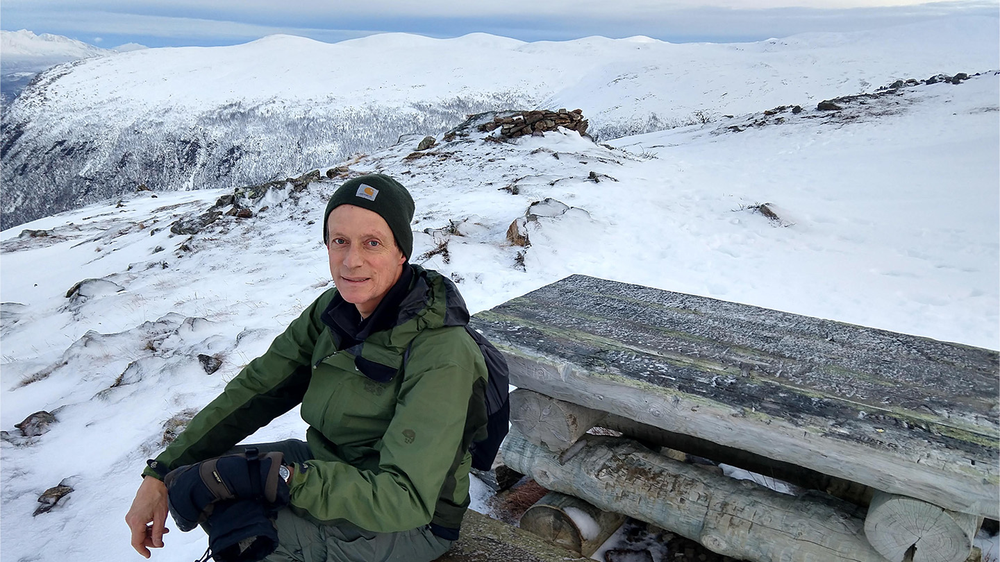 Christopher Preston sits at a picnic table in front of snowy mountains.