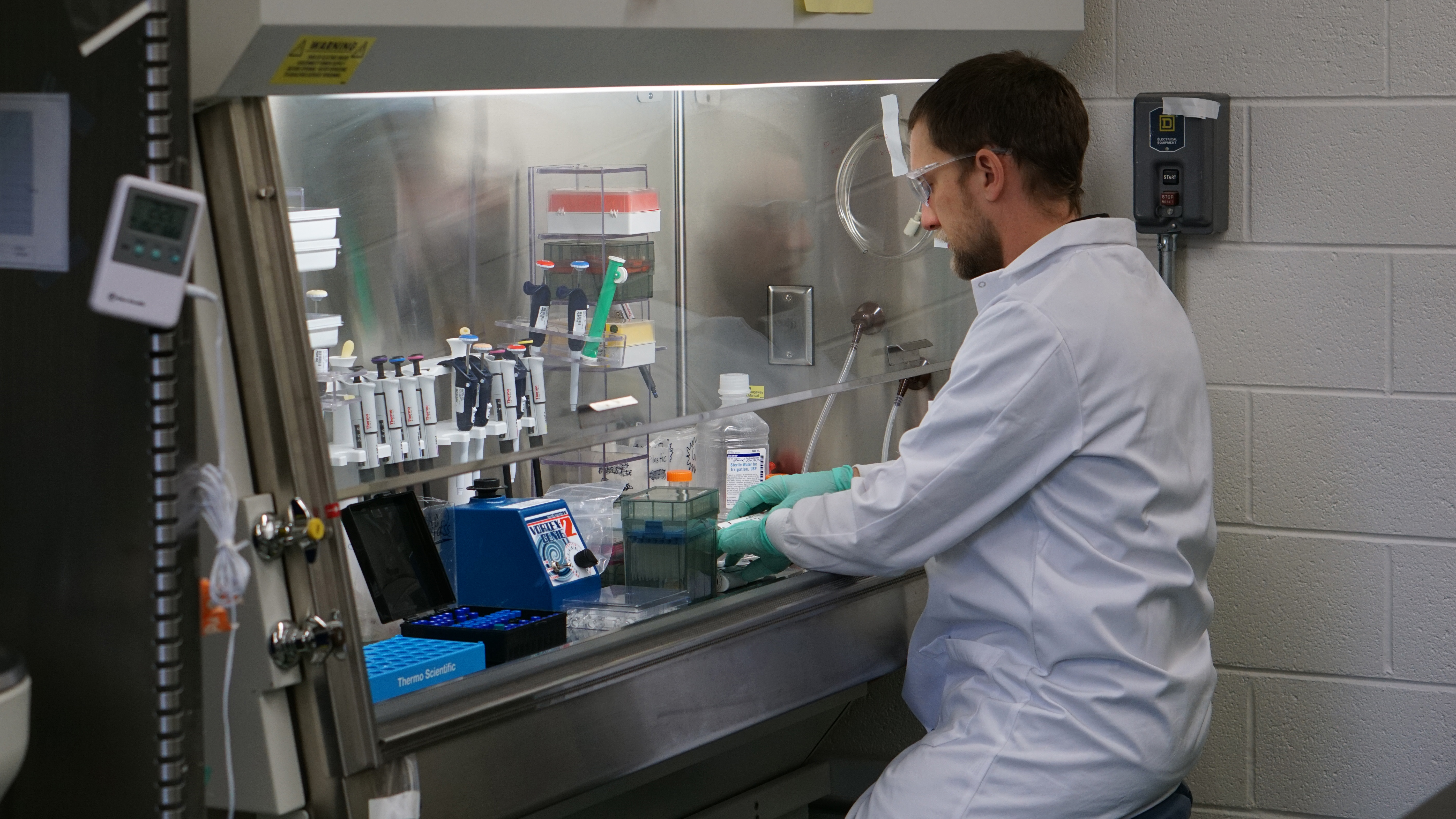 Kris Short working in a laboratory, seated at a lab work station.