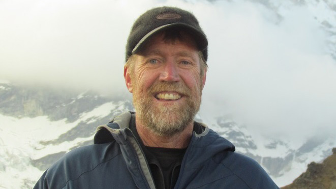 Dr. L. Scott Mills stand smiling in front of a cloudy mountain landscape.