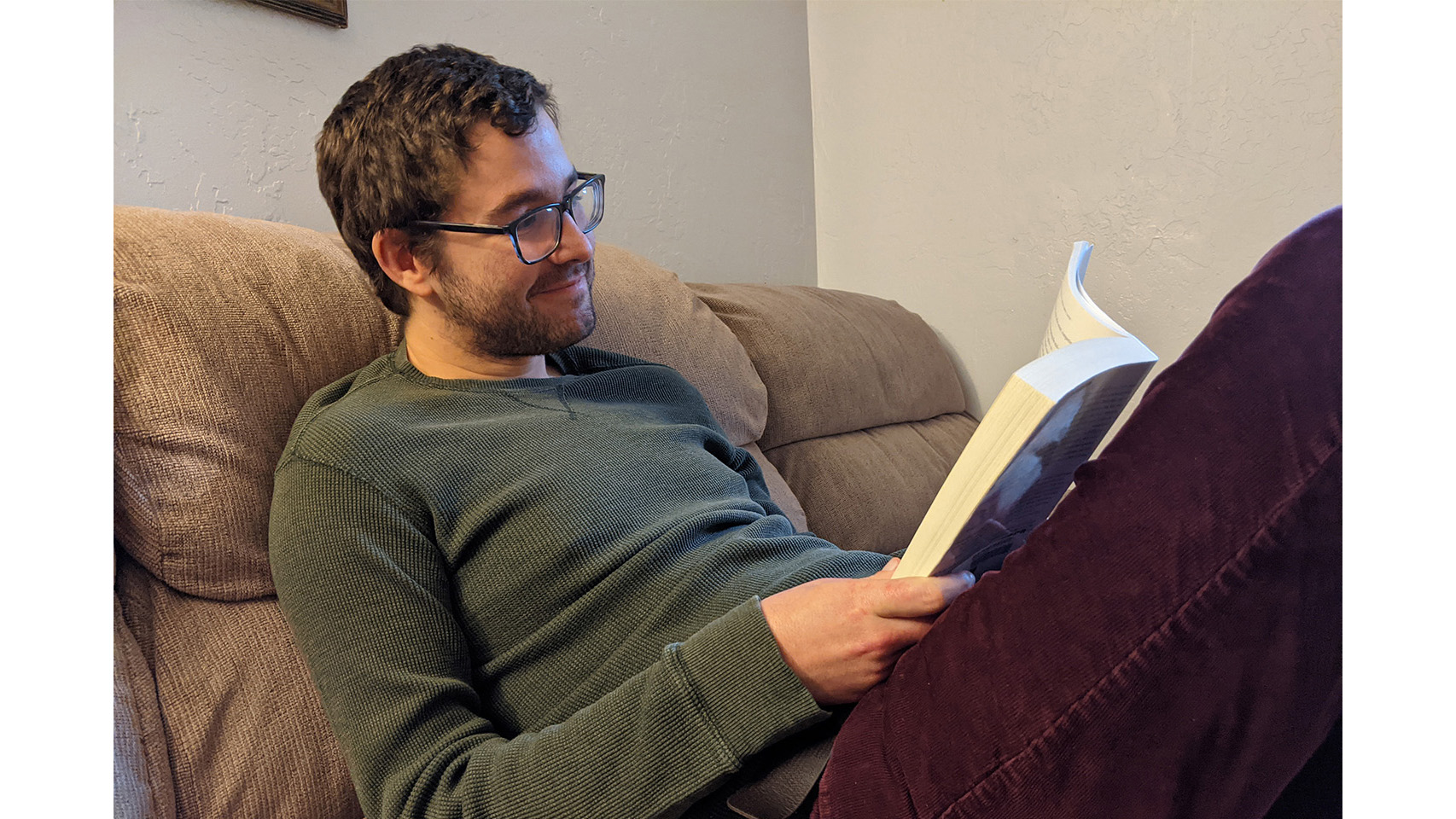 Photo of Dillon Sarb sitting on a couch and reading.
