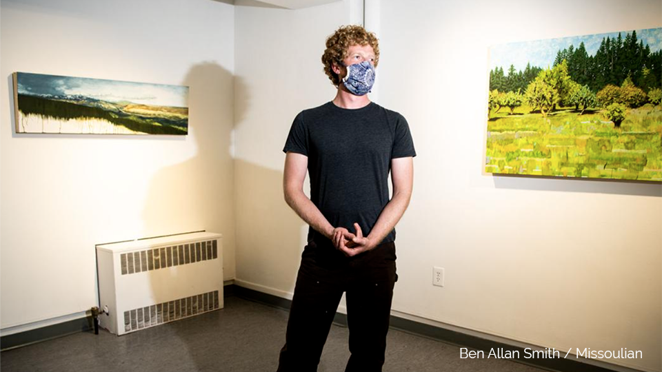 Portrait of Eric Jensen standing in an art gallery with two of his paintings.