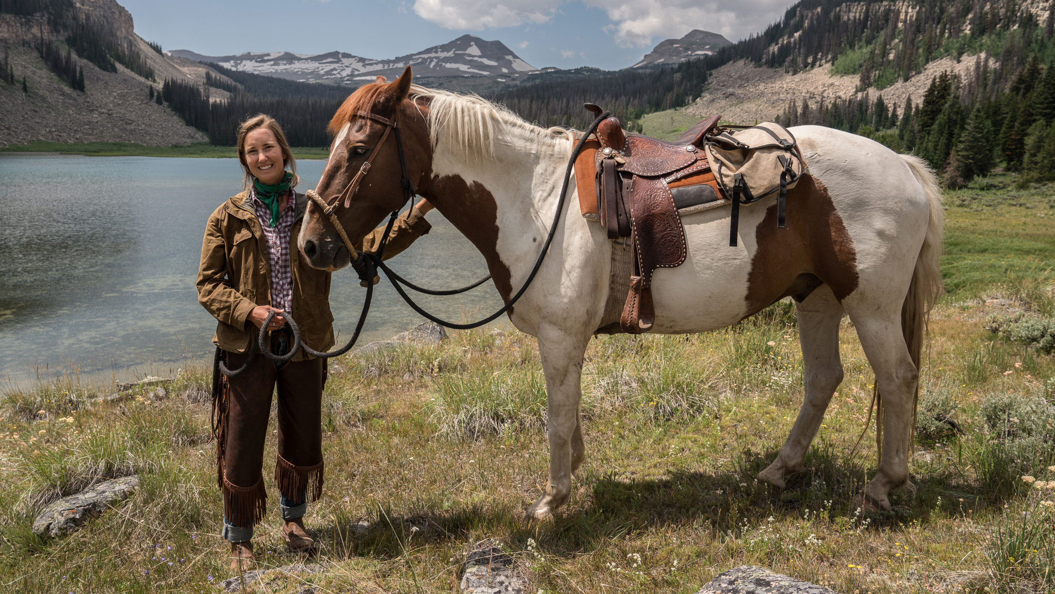 Portrait photograph of Louise Johns standing next to a horse in a mountain landscape with a lake in the background.