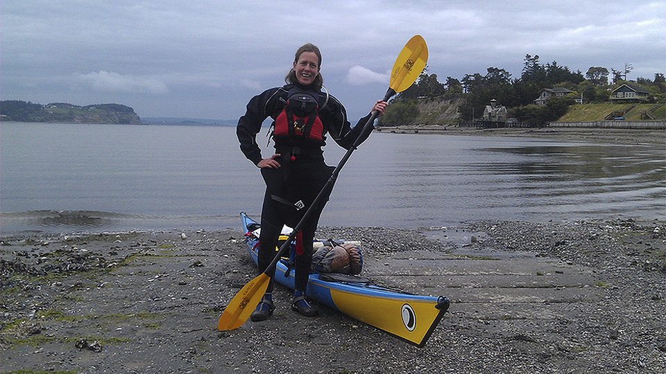 Nadia White poses in front of a kayak on a rocky beach.