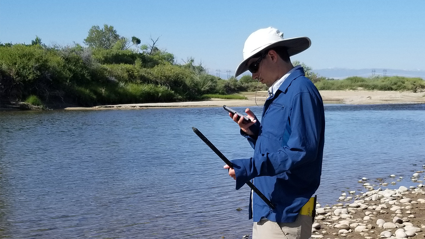 Photo of Nick Thiros standing beside a river checking a handheld measuring device.