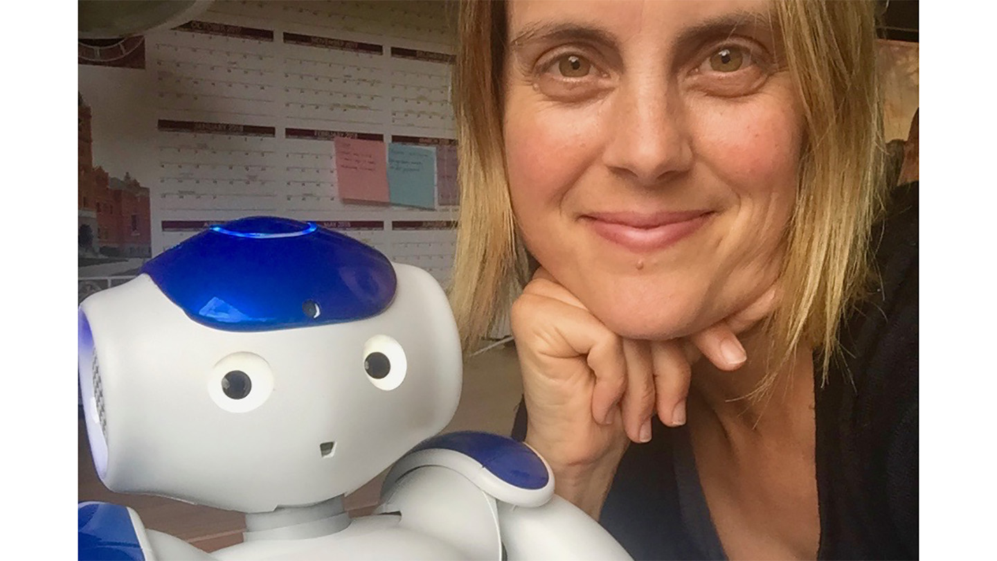 Portrait of Rachel Severson with a small white robot.
