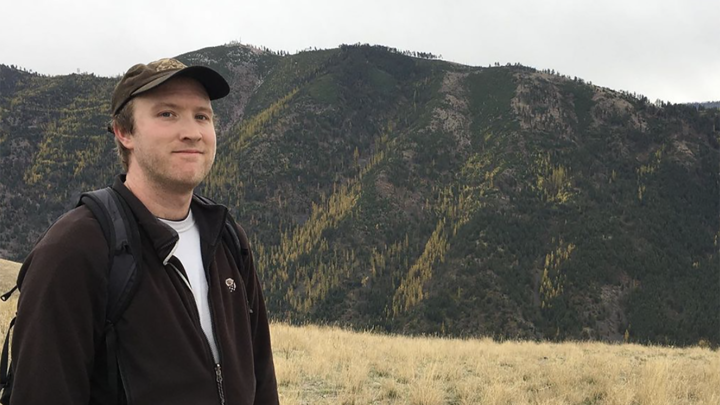 Photo of man smiling with hills in background.