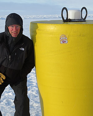 Michael DeGrandpre poses with a research buoy deployed through the ice in the Canada Basin of the Arctic Ocean.