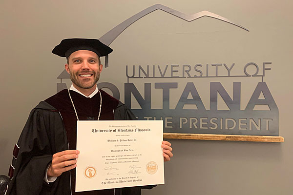 UM President Seth Bodnar holds a degree in his Commencement regalia.