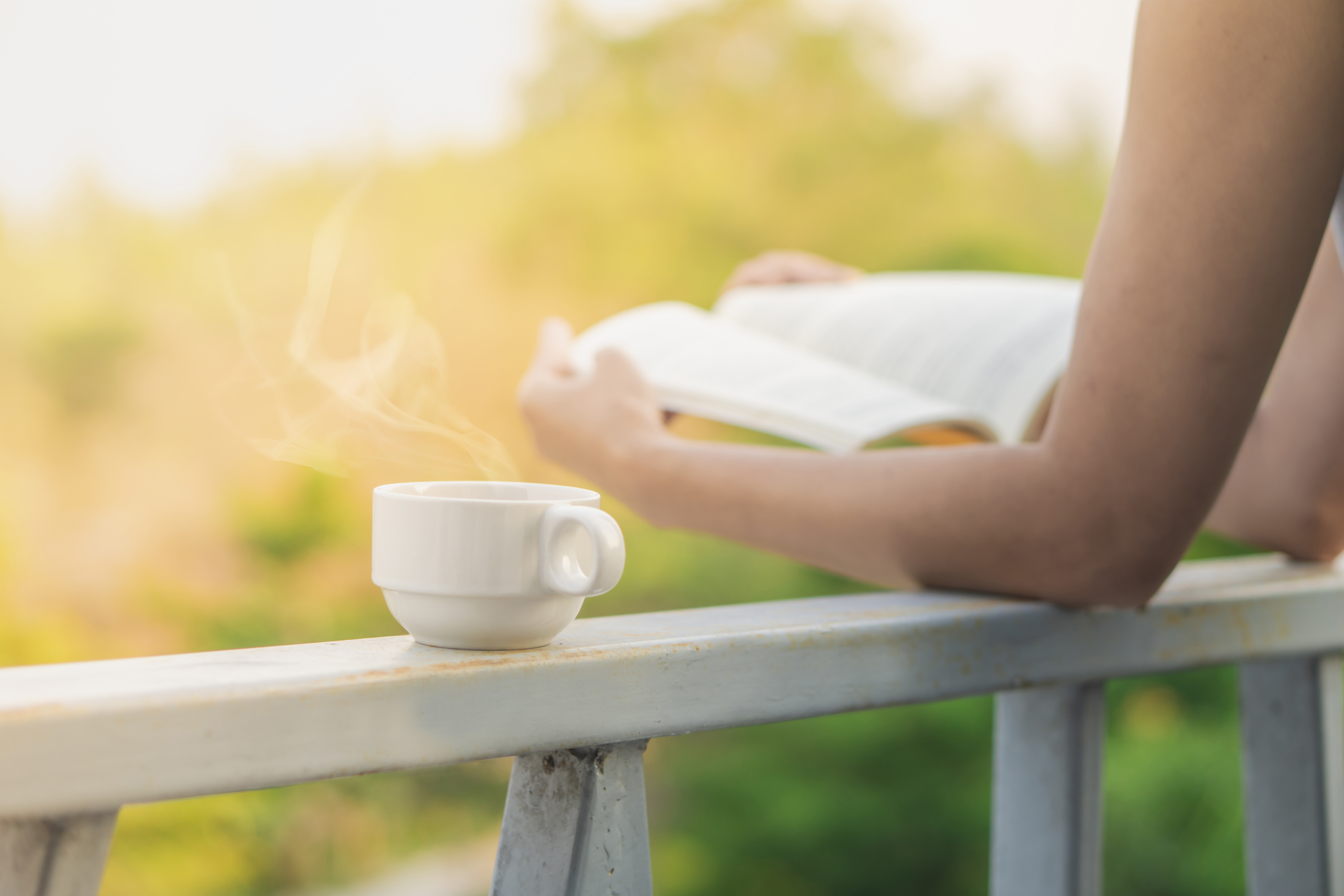 cup hot coffee with woman reading book outdoor