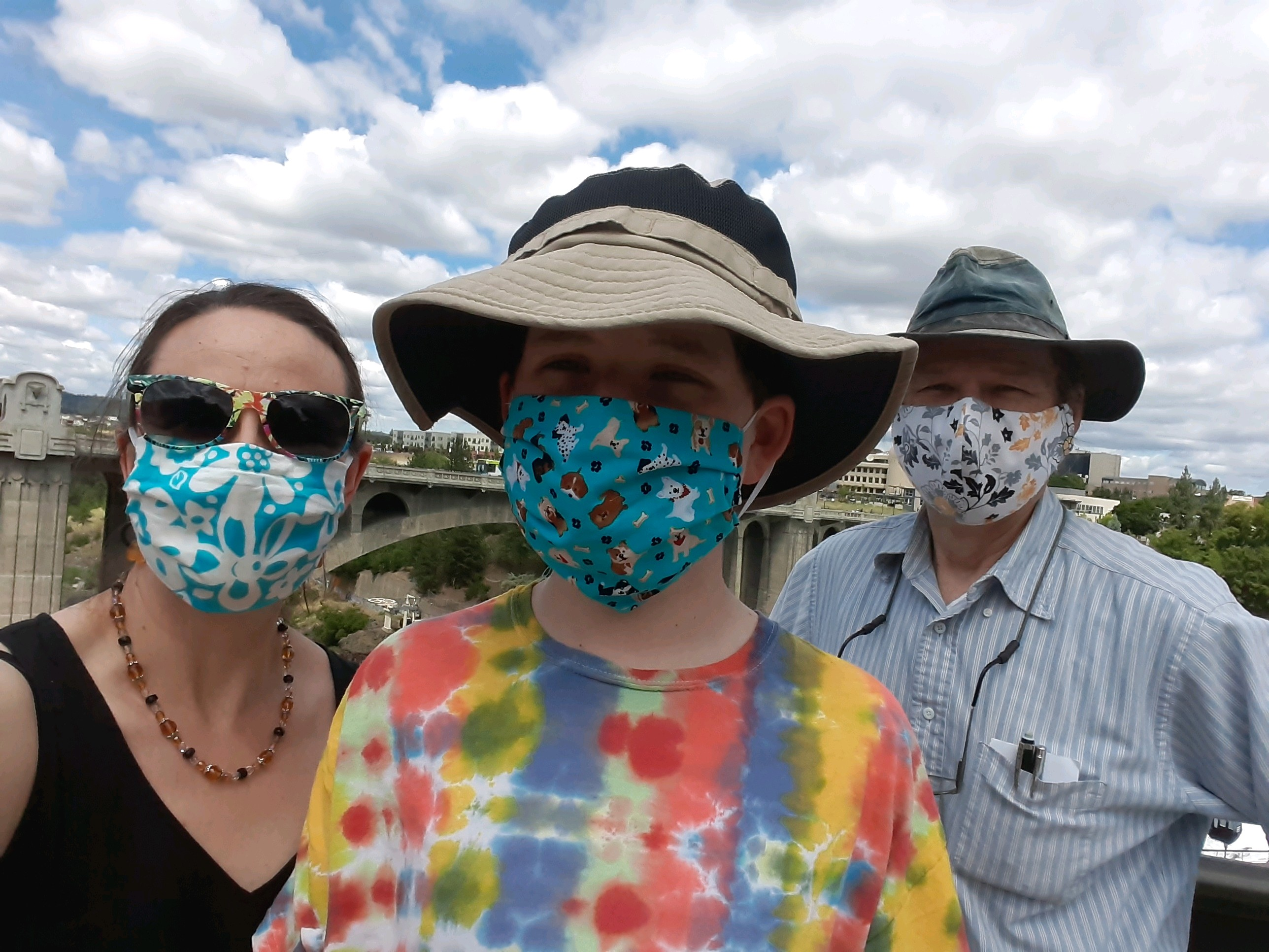 a boy with his parents all wearing masks