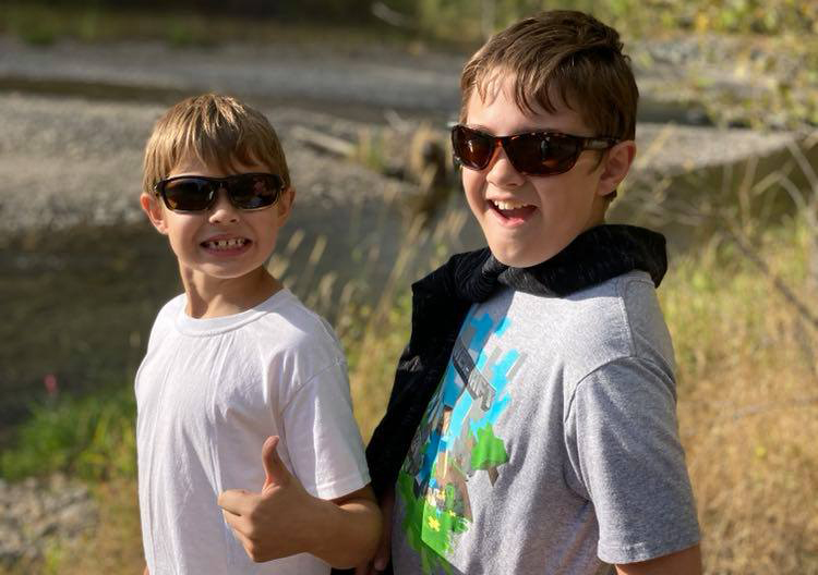 Two boys wearing sunglasses and smiling