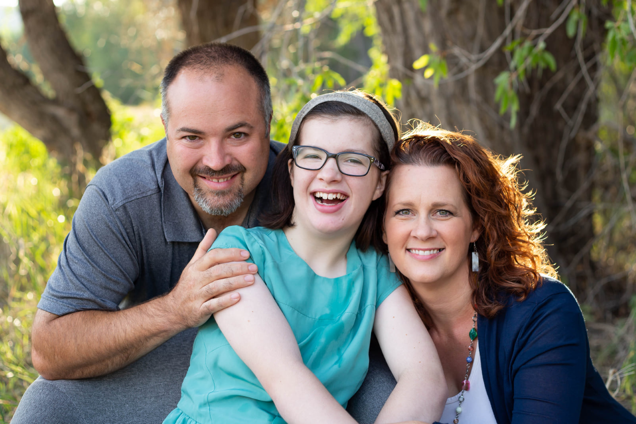 A girl with her parents all smiling