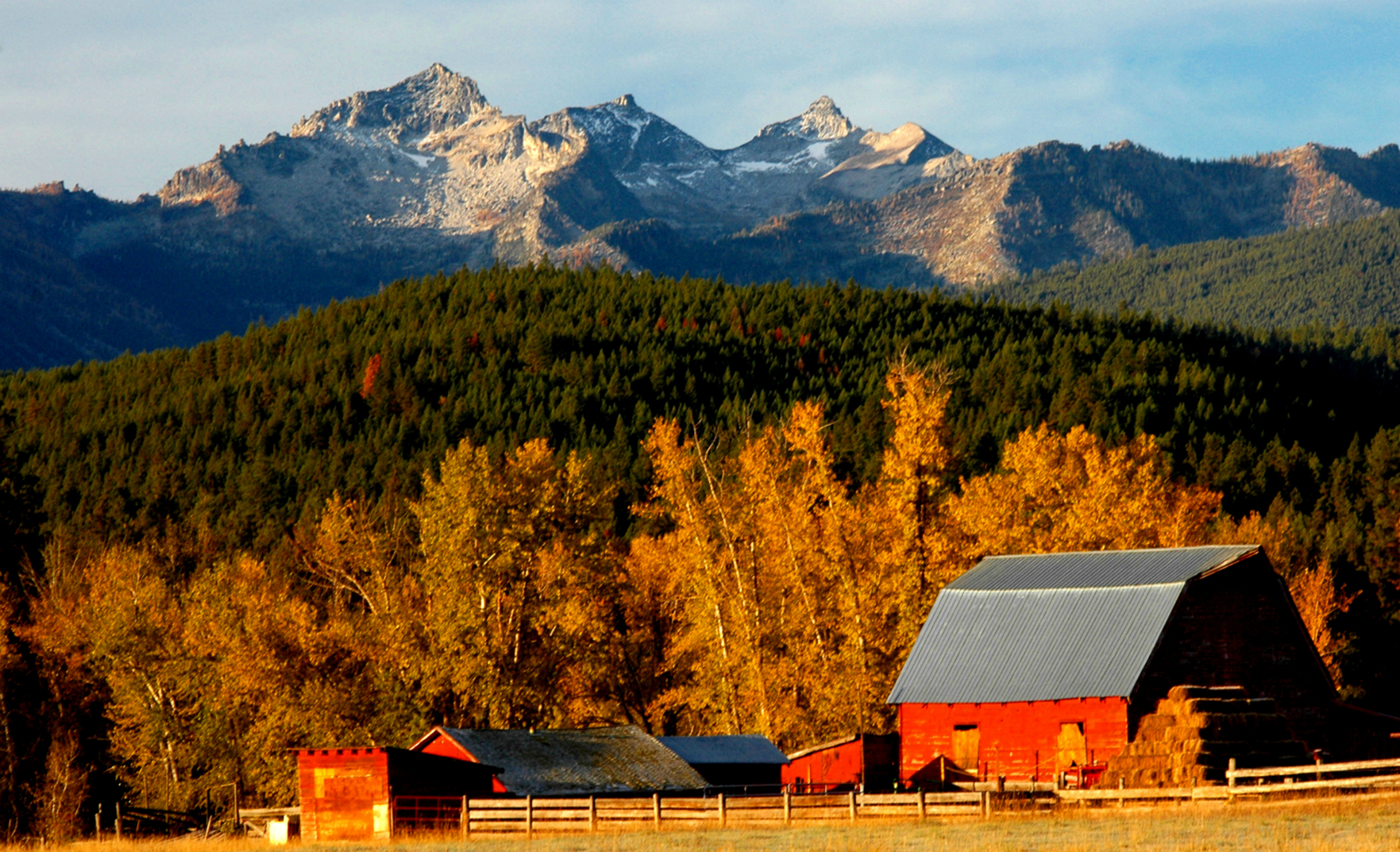 A red barn sits at the base of rolling hills and peaks, all covered in golden sunlight.