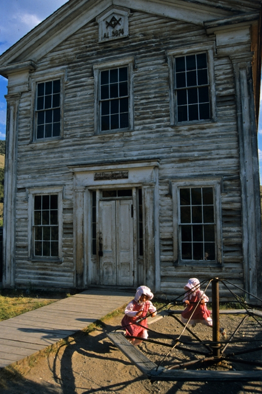 Girls in period dress play before the Bannack Masonic Hall and first school house. (Photo by Rick and Susie Graetz)