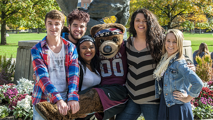 Friends pose in front of the Griz statue near the UM Oval