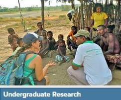 Student sitting and talking to local people in research abroad trip