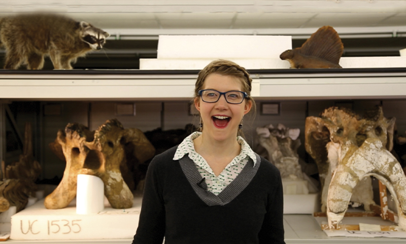 """Screenshot of Emily Graslie on the Youtube show """"The Brain Scoop,""""  standing in front of several animal skeletons looking excited"""