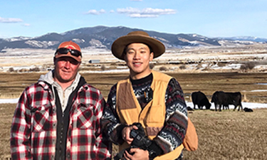 student filmmaker stands next to rancher. Cows, plains, and mountain in background.