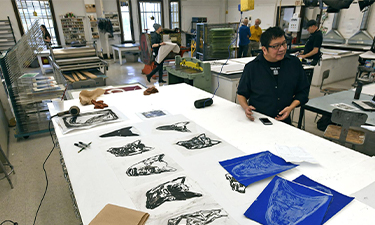 Duane Slick, a faculty member at the Rhode Island School of Design, sitting at table with contemporary indigenous prints