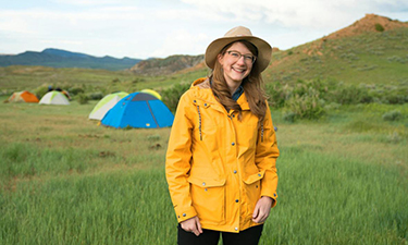 Emily Graslie in field gear standing in front of a green field with tents set-up behind her. Just outside Hanna, Wyoming.
