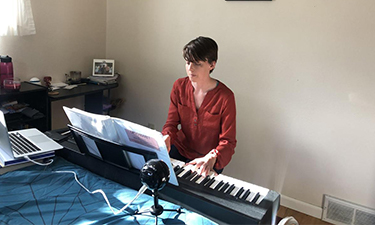 student Jane Best playing piano in her home